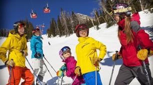 Family skiing with Jackson Hole gondola in the background