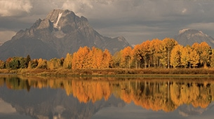 The Grand Tetons with fall colors and a lake.