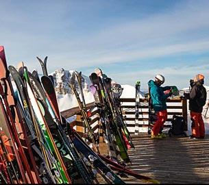 Skis up again a railing.